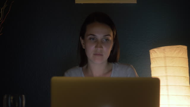 молодая истощенная, подавленная, сосредоточенная женщина сидит в своей комнате или офисе с окнами в темноте у лампы. учеба поздно ночью. не � - работа допоздна стоковые видео и кадры b-roll