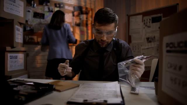молодой эксперт описывает нож доказательства от разбить и захватить преступной сцене - expert стоковые видео и кадры b-roll