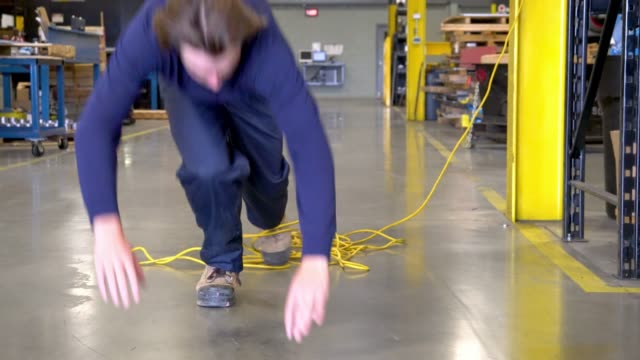 A young factory worker trips on an electrical cord.