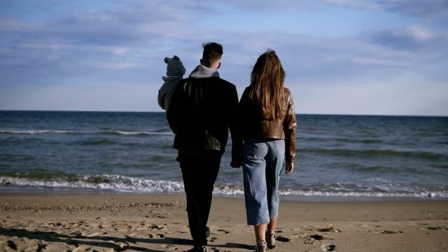 息子を抱えた父親の若い家族は、海岸沿いのスワの海岸を歩きます。幸せな家族が海岸沿いを歩き、手をつないで歩きます。レアビュー - 春のファッション点の映像素材/bロール