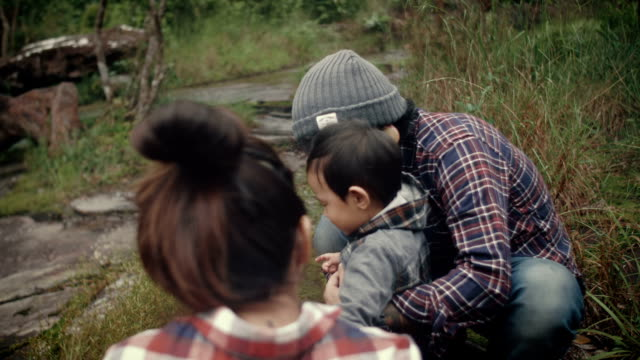 Young family and son sitting on rock in forest at Thailand. video