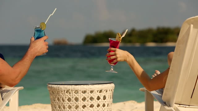 Young family couple sunbathing and drinking colored cocktail on tropical beach. Lovers on honeymoon on exotic vacation lying in the sun on deck chairs near ocean on vacation video