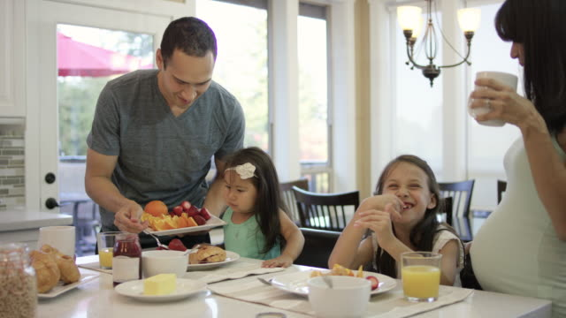 Young family eating breakfast together in the kitchen video