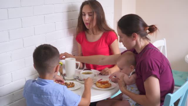 junge familie mit frühstück gemeinsam in der küche zu hause - alleinerzieherin stock-videos und b-roll-filmmaterial