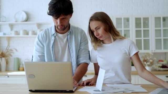 vidéos et rushes de jeune famille ayant des problèmes d'endettement. femme et homme étudiant la banque de forme de papier tout en gérant le budget domestique ensemble dans l'intérieur de cuisine - bec