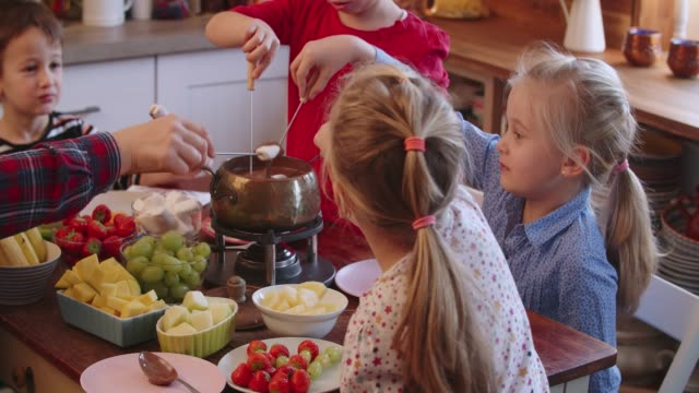 young family having delicious chocolate fondue in a pot served with fruits - pietanza cotta in tavola video stock e b–roll