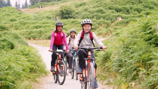 Young family having fun riding mountain bikes on a camping holiday, close up, front view, Lake District, UK