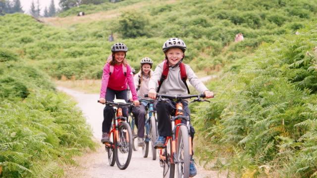 vídeos y material grabado en eventos de stock de familia joven divertirse montar bicicletas de montaña en unas vacaciones en camping, cerrar, vista frontal, lake district, uk - montar