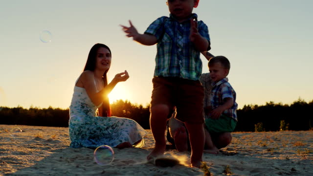 Young family having fun together - parents with two sons blow bubbles video