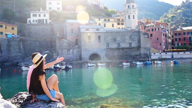 Família jovem numa enseada em uma pedra na reserva Cinque Terre. Natureza deslumbrante e ar fresco - vídeo