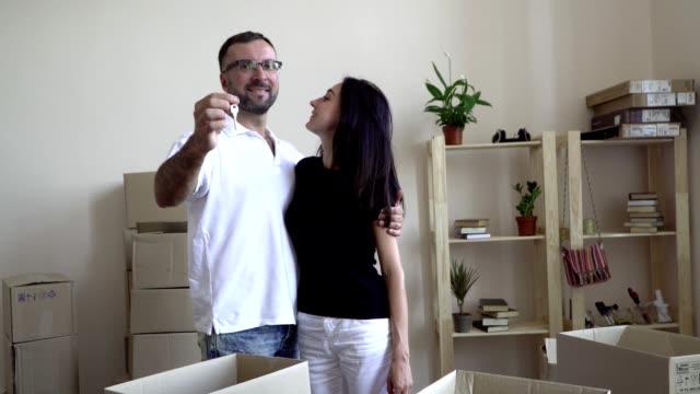 stockvideo's en b-roll-footage met een jong gezin gaat. een man in bril en een wit t-shirt knuffels zijn dark-haired vrouw, die klampt zich aan zijn schouder vast. in de handen van de man houdt de toetsen naar het nieuwe appartement en zijn vrouw te kussen - wit t shirt