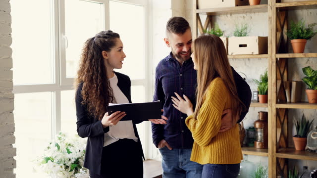 young family is talking to housing agent inside new flat about purchasing real estate, hugging and gesturing emotionally. moving house and buying property concept. - mostrare video stock e b–roll