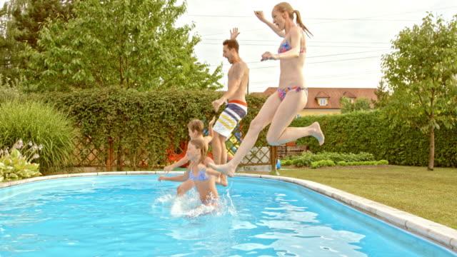 vídeos y material grabado en eventos de stock de cámara lenta de familia de ts salto junto a la piscina - backyard pool
