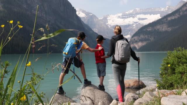 giovane famiglia guardare attraverso lake louise, in escursione - berretto video stock e b–roll
