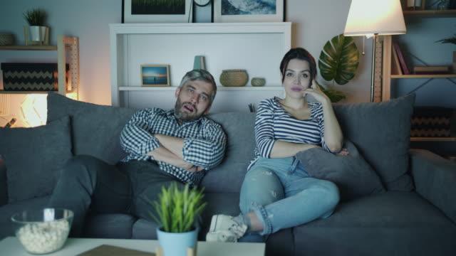 stockvideo's en b-roll-footage met jonge familie man en vrouw kijken saai film op tv thuis 's nachts yadrinking - couch