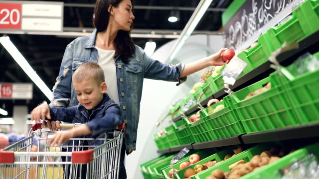 vídeos de stock e filmes b-roll de young family mother and son are buying fruit in grocery store, they are taking pears and kiwifruit and putting them in trolley. happy customers and supermarket concept. - kiwi