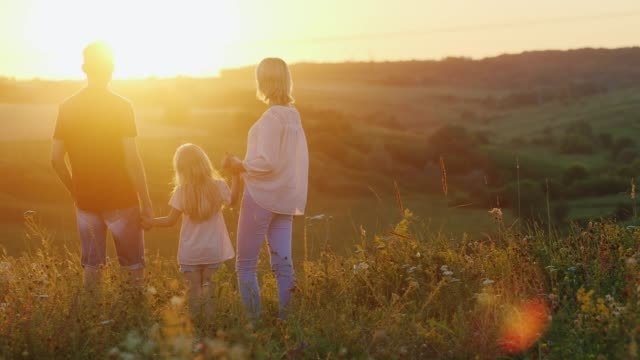 young family of three people enjoying the sunset on a cliff - природный парк стоковые видео и кадры b-roll