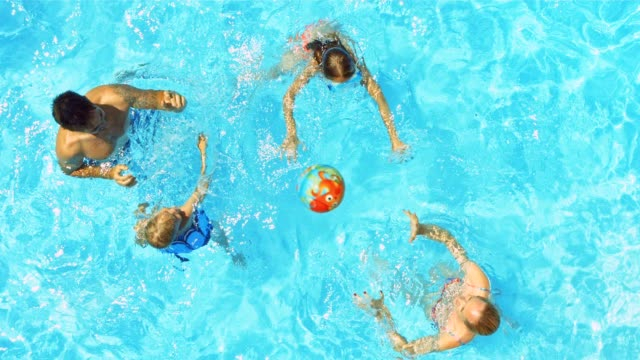 A young family playing ball in the pool on a sunny day video