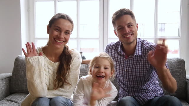 young family sitting on couch waving hands looking at camera - sventolare la mano video stock e b–roll