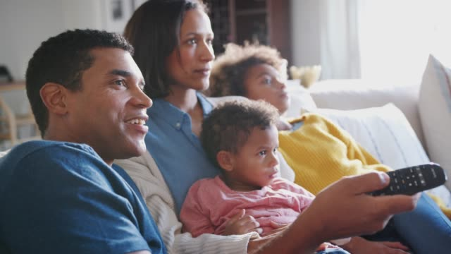 Young family sitting together on the sofa in their living room watching TV, close up, side view Young family sitting together on the sofa in their living room watching TV, close up, side view watching tv stock videos & royalty-free footage