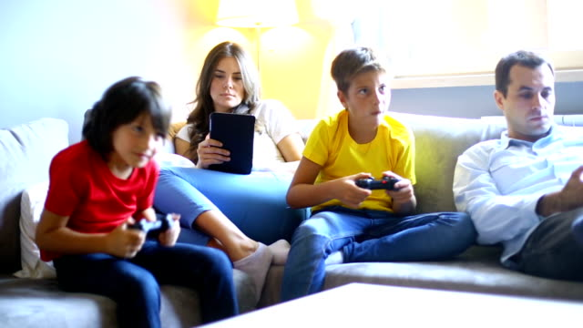 Young family sunday routine. Mid 30's husband and wife with their two sons, aged 6 and 9, spending sunday afternoon at home. They are sitting on the couch, mom and dad are using their smartphones and tablets, and kids are playing video game. laziness stock videos & royalty-free footage