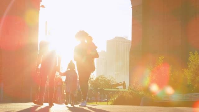 マンハッタン、バックライト付きの橋の下を歩く若い家族 - 米国旅行点の映像素材/bロール