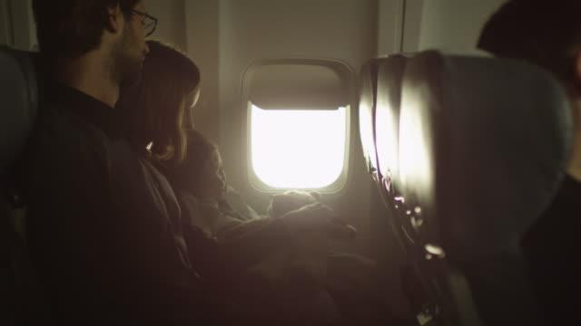 Jeune famille avec un garçon assis à l'intérieur d'un avion à côté d'une fenêtre. - Vidéo