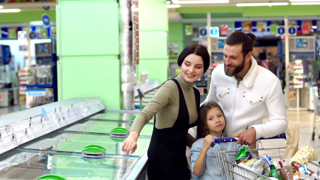 A young family with a child in the supermarket choose frozen foods.