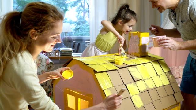 ung familj med barn bygga och måla leksak kartong hus tillsammans - konsthantverk bildbanksvideor och videomaterial från bakom kulisserna