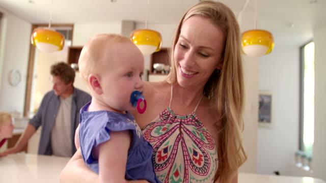 vídeos de stock, filmes e b-roll de família jovem com filha de mãe com bebê - bico