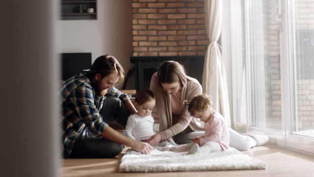 Young family with two baby girls spending time together at home Young couple with two daughters spending time together at living room living room stock videos & royalty-free footage