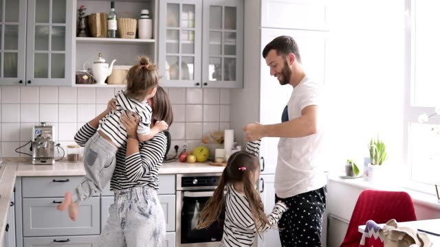 young family with two daughters are dancing on the kitchen - kitchen filmów i materiałów b-roll
