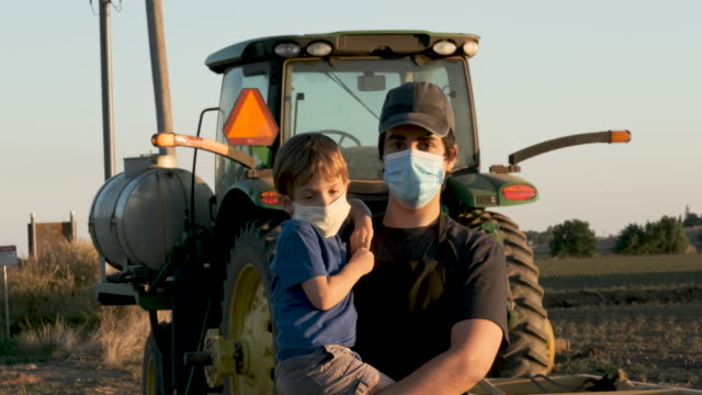 Young farmer posing with his son, both wearing protective face masks