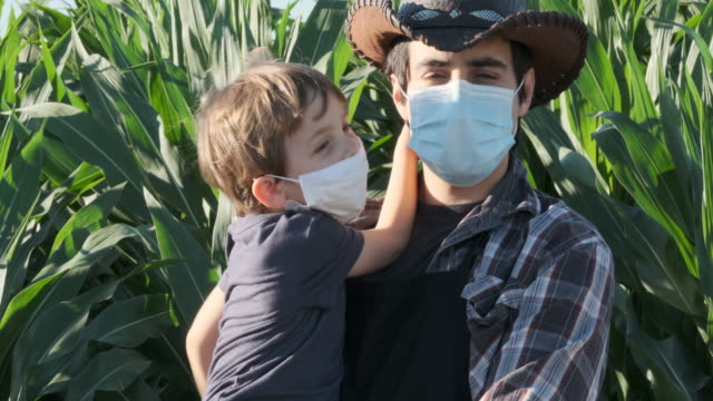 Video Young farmer posing with his son, both wearing protective face masks