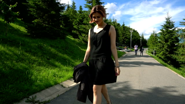 Young fashion beautiful woman walking in a park, summer time Young fashion beautiful woman walking in a park, summer time. Fly cam. short length stock videos & royalty-free footage
