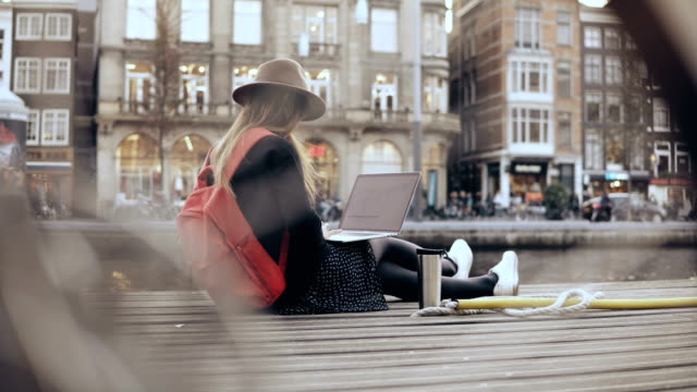 4K Young fashion blogger sitting with laptop. Creative worker outdoors. Freedom. Lifestyle shot through a bicycle wheel video