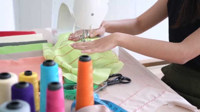 young fashion designer sewing new collection in clothing studio - macchina per cucire video stock e b–roll