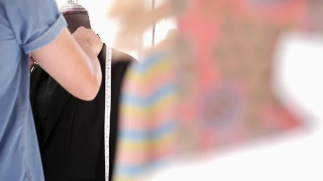 Young fashion designer, tailor and dressmaker adjusting clothes on tailoring mannequin