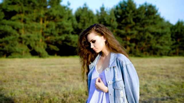 young fashion woman is wearing summer dress and jacket is walking near a forest in summer sunny evening video