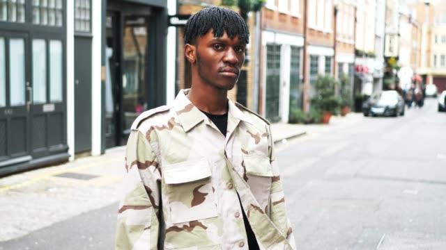 vidéos et rushes de jeune homme noir à la mode à londres, dans la veste de camouflage - mode londres