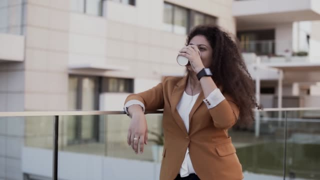 Young fashionable entrepreneur enjoying cup of coffee during work break