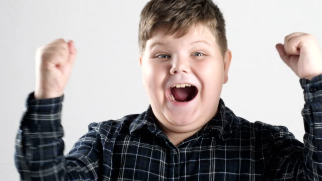 young fat boy rejoices in victory 50 fps - gastronomico video stock e b–roll