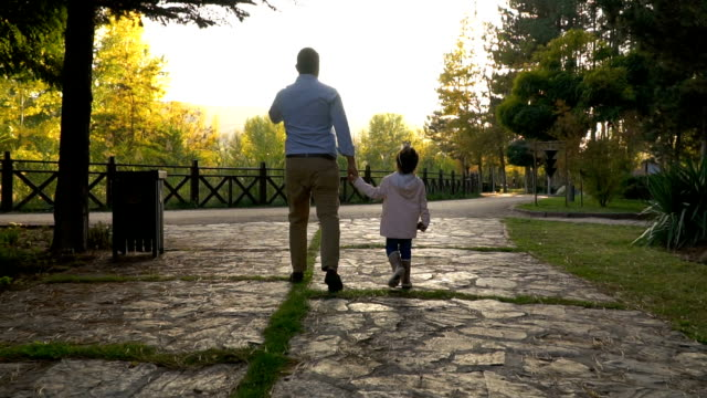 young father and daughter walking in public park - padre single video stock e b–roll
