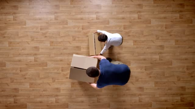 stockvideo's en b-roll-footage met jonge vader en zoon verhuizen naar leeg huis met dozen, top shot, kleine jongen uitgevoerd en knuffelen, papa, vader spinnen zoon, houten parketvloer - bovenkleding