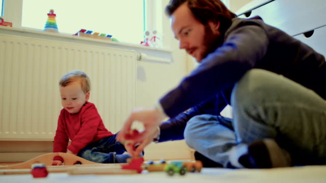 Young father and son playing at home video