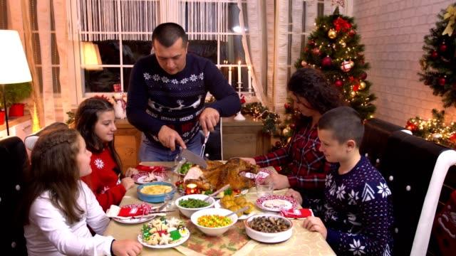 young father carving stuffed roasted turkey for christmas dinner - indyk pieczony filmów i materiałów b-roll