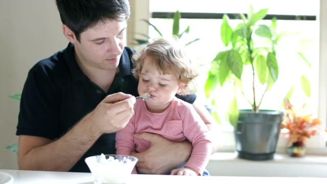 Young father feeding his cute little daughter video