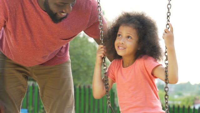 Young father gently swinging his little beautiful daughter in backyard, love Young father gently swinging his little beautiful daughter in backyard, love princess stock videos & royalty-free footage