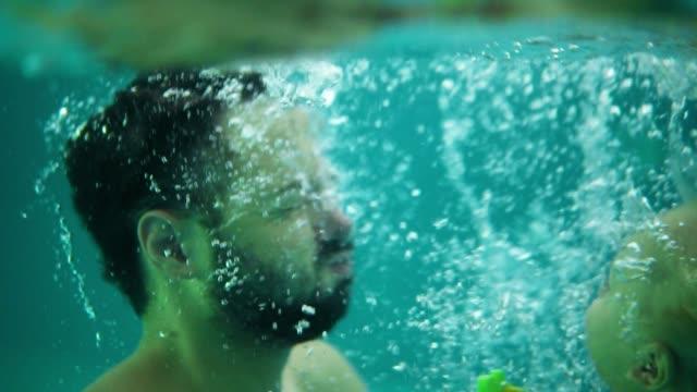 vídeos y material grabado en eventos de stock de joven padre es levantar a su niño del agua mientras le enseña a nadar en la piscina. niño feliz y su padre son risa y te diviertes - madre e hijos