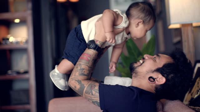 Un padre joven acostado en el sofá - vídeo